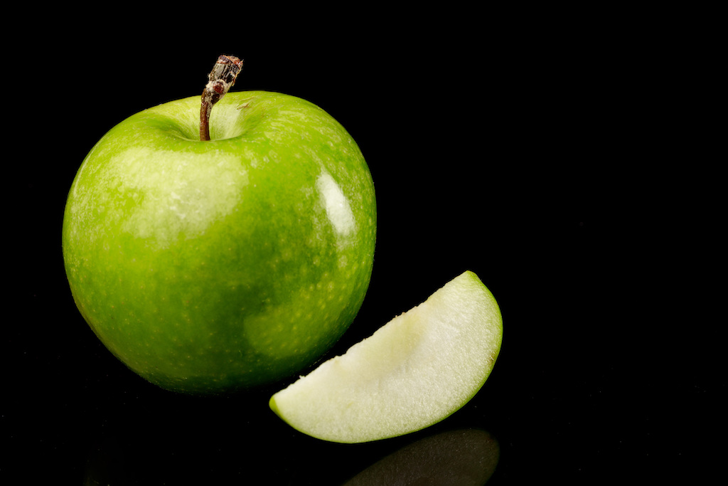 manzana verde sobre fondo negro